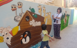Woman standing next to a kids mural